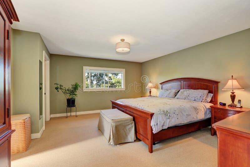 Ansicht des hölzernen Betts Königgröße im olivgrünen Schlafzimmerinnenraum lizenzfreies stockfoto