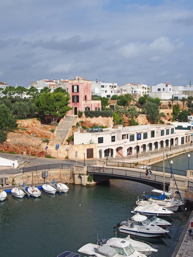 Ansicht des Hafens in ciutadella menorca mit festgemachten Booten und umgebenden Gebäuden im blauen Sommersonnenlicht stockfotos