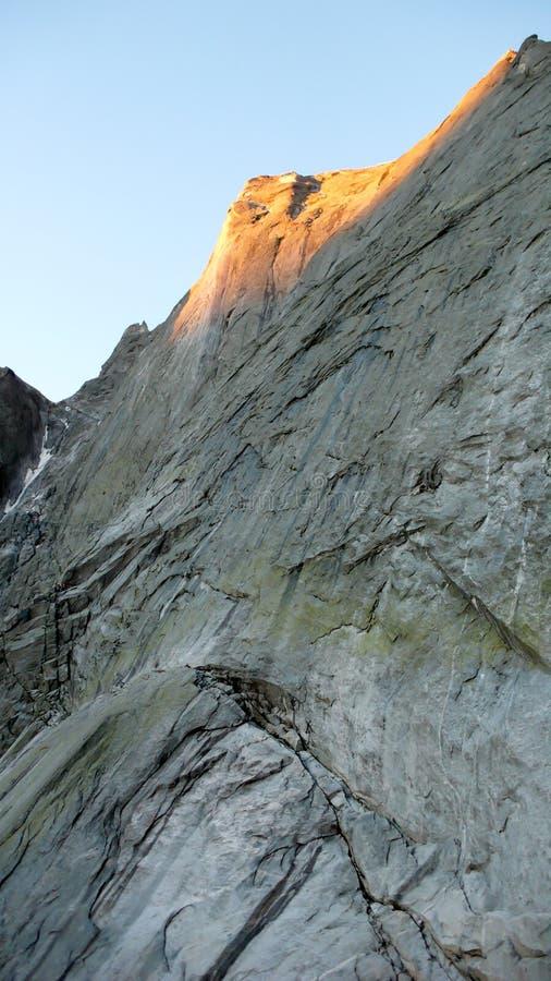 Ansicht des klassischen Nordostgesichtes von Pizzo Badile und seine vielen kletternden Wege mit einem Bergsteiger, der das berühm lizenzfreie stockbilder