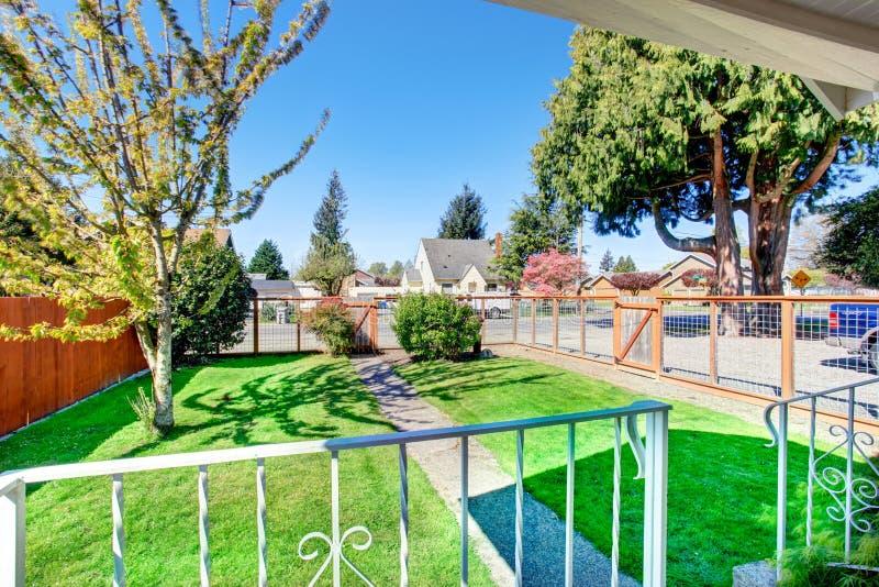 Ansicht des kleinen Vorgartens mit schmalem konkretem Gehweg und grünem Rasen lizenzfreies stockfoto