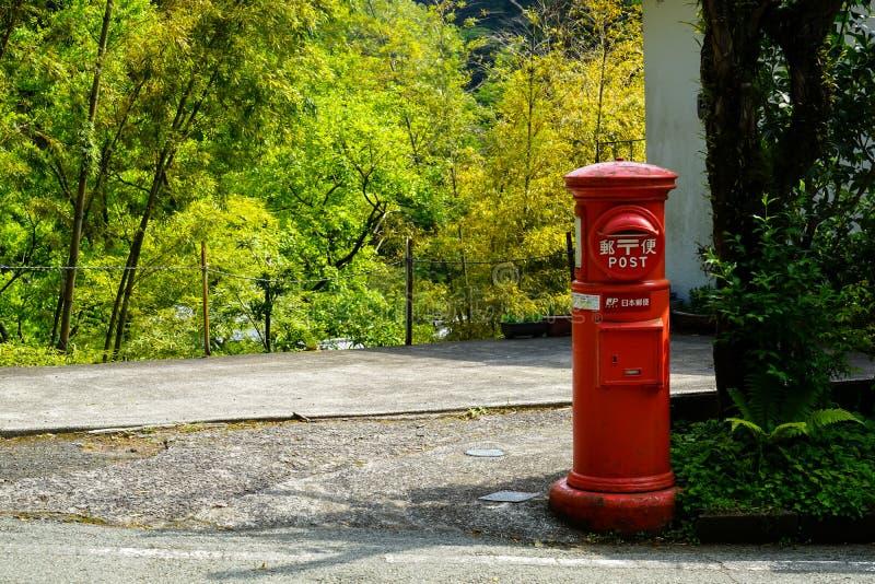 Ansicht des lokalen roten Postbox, der auf lokaler Straße mit Grünpflanze, Baum und neuem hellgrünem Bambushintergrund in Kurokaw lizenzfreies stockfoto