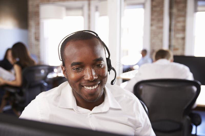 Ansicht des Mannes arbeitend im beschäftigten Kunden-Kundendienst stockfotografie