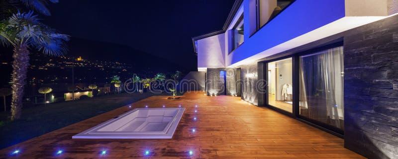 Ansicht des modernen Landhauses in der Nacht mit Pool lizenzfreie stockfotografie
