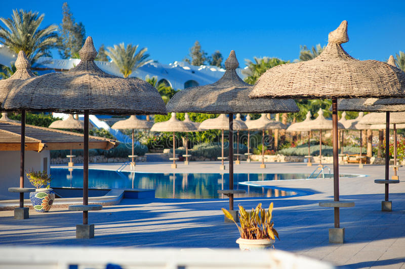 Ansicht des Pools mit Palmen und mit Stroh gedeckten Regenschirmen stockfotos