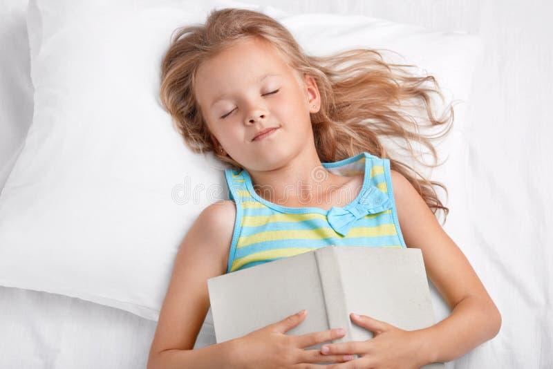 Ansicht des reizenden Mädchens mit dem langen hellen Haar schläft nach Ablesenmärchen, hält Buch auf Magen, liegt im bequemen wei stockbilder