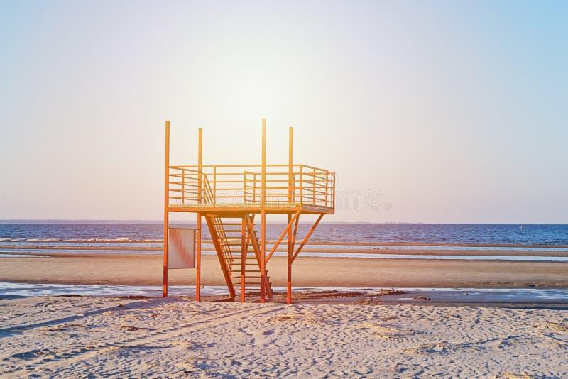 Ansicht des sandigen Strandes des Sonnenuntergangs mit rotem leerem modernem Leibwächterturm stockfotos