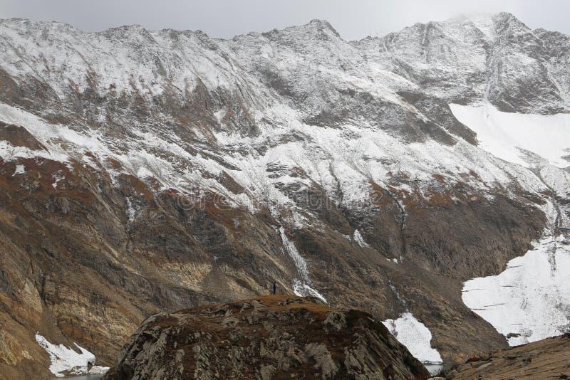 Ansicht des schneebedeckten hügeligen Berges unter dunklen Wolken stockbilder