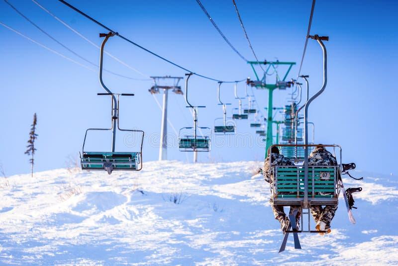 Ansicht des Skiaufzugs und der Schnee-mit einer Kappe bedeckten Berge lizenzfreies stockfoto