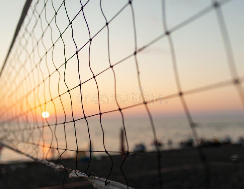 Ansicht des Sonnenaufgangs durch das Volleyballnetz Früher Morgen, drastischer Sonnenaufgang über Meerwasser stockfotos