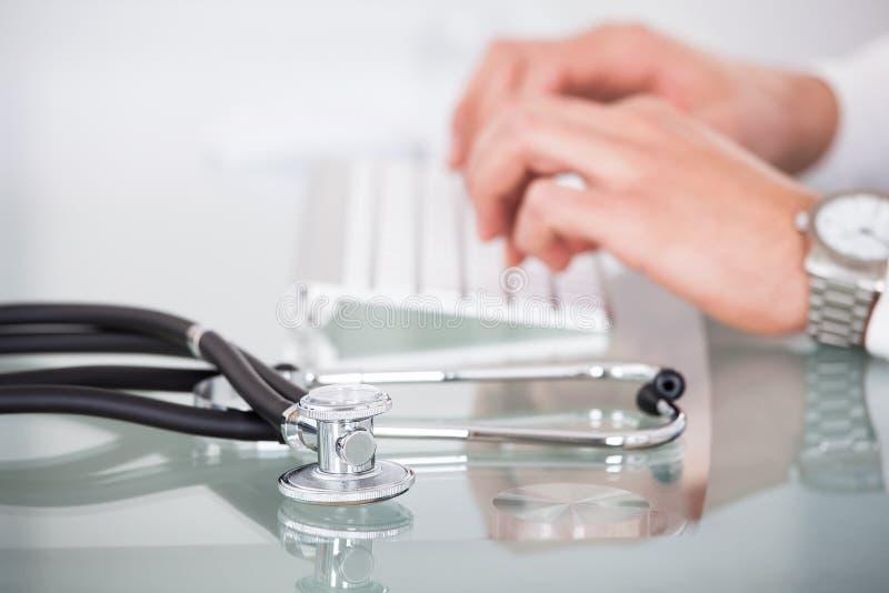 Ansicht des Stethoskops mit Doktor, der Computertastatur verwendet stockfotos