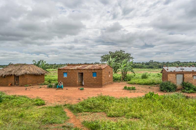 Ansicht des traditionellen Dorfs, alter Mann, der vor mit Stroh gedecktem Haus mit Dach- und Terrakotta- und Strohwänden sitzt stockfotos