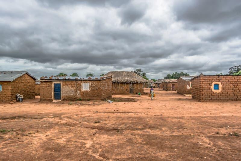 Ansicht des traditionellen Dorfs, der tragenden Wasserbehälter der Frau auf Weg, der mit Stroh gedeckten Häuser mit Dach und der  stockbild