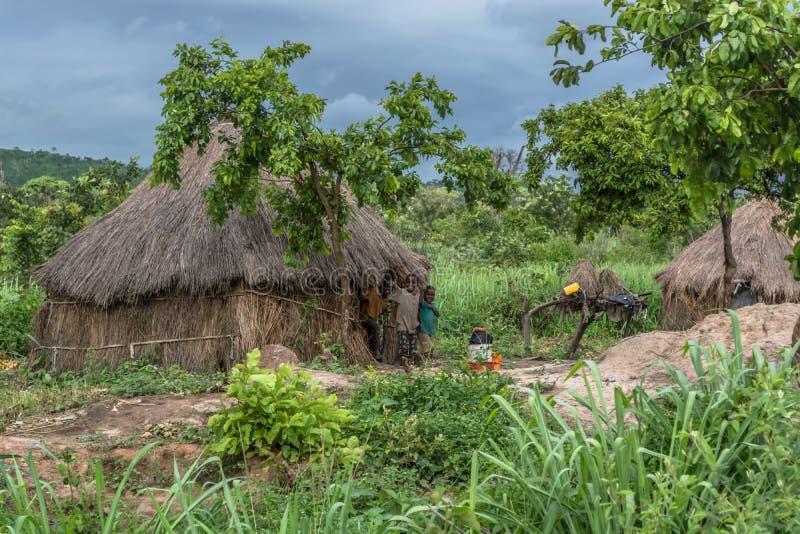 Ansicht des traditionellen Dorfs, Kindergruß auf mit Stroh gedecktem Haus mit Dach- und Terrakotta- und Strohwänden lizenzfreies stockbild