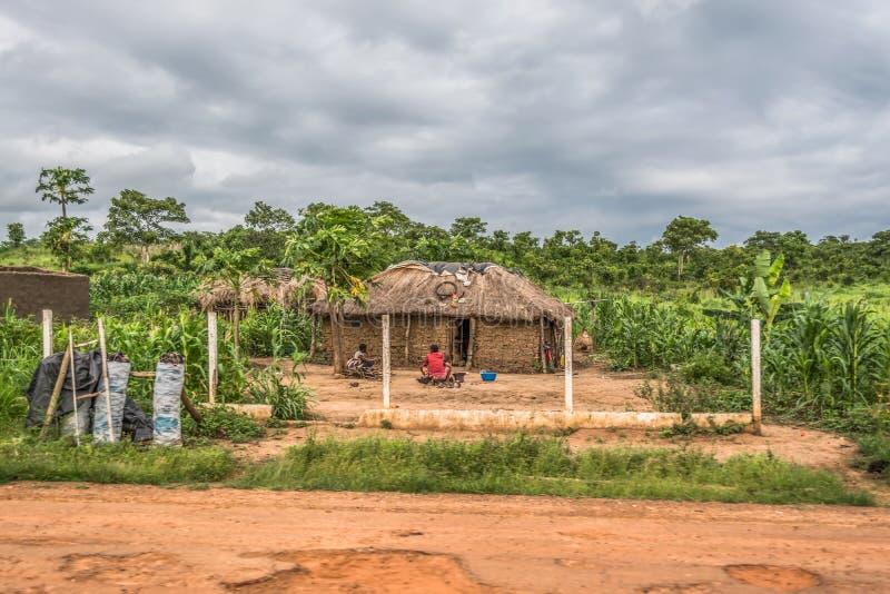 Ansicht des traditionellen Dorfs, zwei Frauen und des Kindes, das vor mit Stroh gedecktem Haus mit Dach- und Terrakotta- und Stro lizenzfreie stockbilder