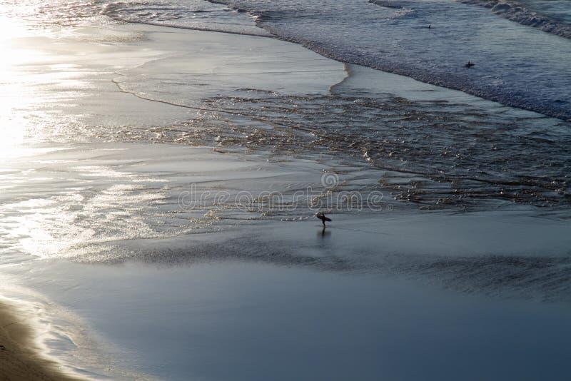 Ansicht des Ufers des Ozeans bei Ebbe Reflexion der Sonne im Ozean, Surfer im Wasser lizenzfreie stockfotografie