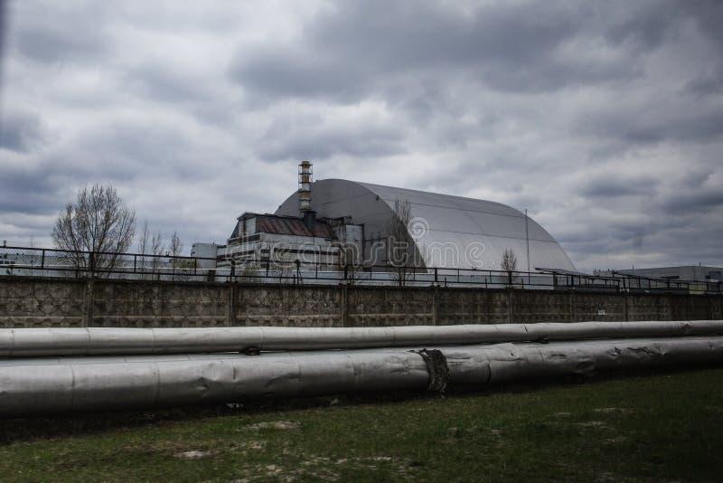 Ansicht des zerstörten Reaktors 4 und des Denkmals für die Tschornobyl-Liquidatoren stockfoto