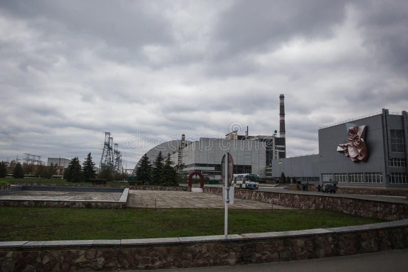 : Ansicht des zerstörten Reaktors 4 und des Denkmals für die Tschornobyl-Liquidatoren stockfotos