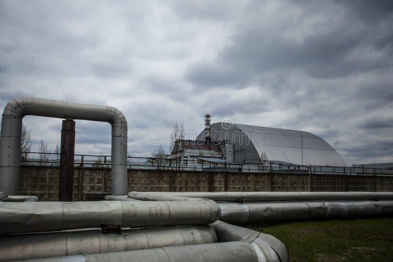 : Ansicht des zerstörten Reaktors 4 und des Denkmals für die Tschornobyl-Liquidatoren lizenzfreies stockfoto