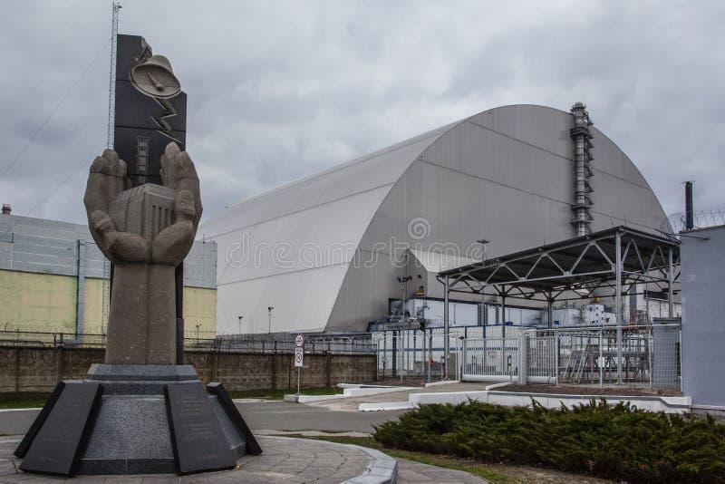: Ansicht des zerstörten Reaktors 4 und des Denkmals für die Tschornobyl-Liquidatoren stockfotografie