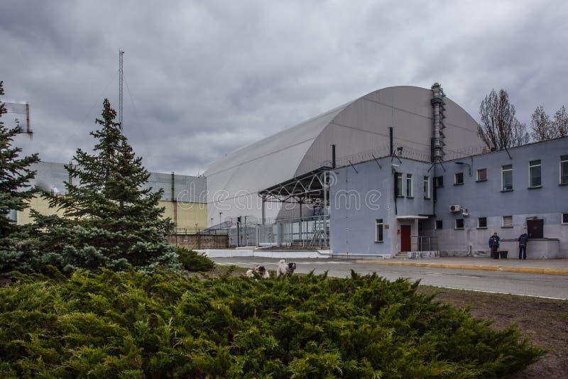 : Ansicht des zerstörten Reaktors 4 und des Denkmals für die Tschornobyl-Liquidatoren lizenzfreie stockfotografie