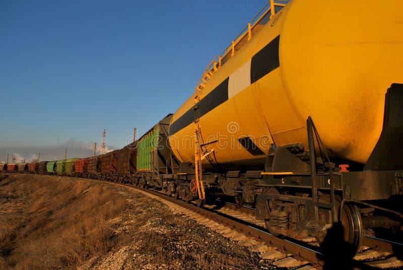 Ansicht des Zugs der Zisternen und der Lastwagen bei Sonnenaufgang gegen den blauen Himmel lizenzfreie stockfotografie