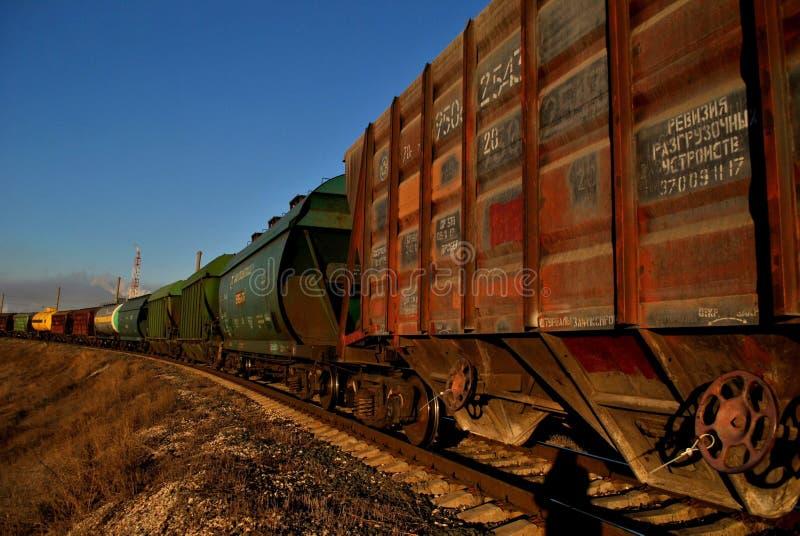 Ansicht des Zugs der Zisternen und der Lastwagen bei Sonnenaufgang gegen den blauen Himmel lizenzfreies stockbild