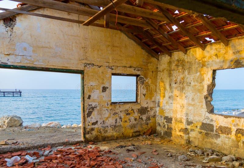 Ansicht durch aufgegebenes Hausfenster durch den Strand lizenzfreies stockbild