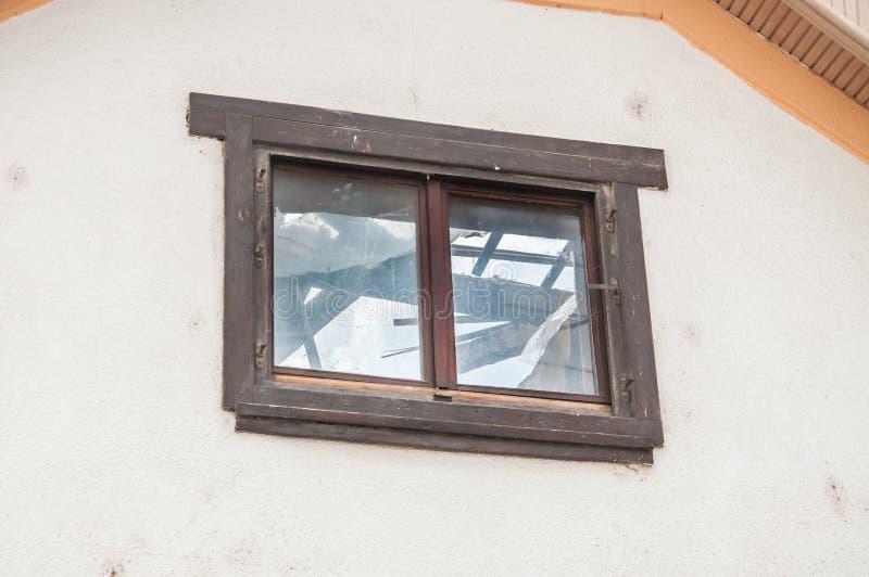 Ansicht durch das Fenster auf dem Haus mit geschädigter und eingestürzter Dachkonstruktion nach Naturkatastrophe der Nachwirkunge stockbild