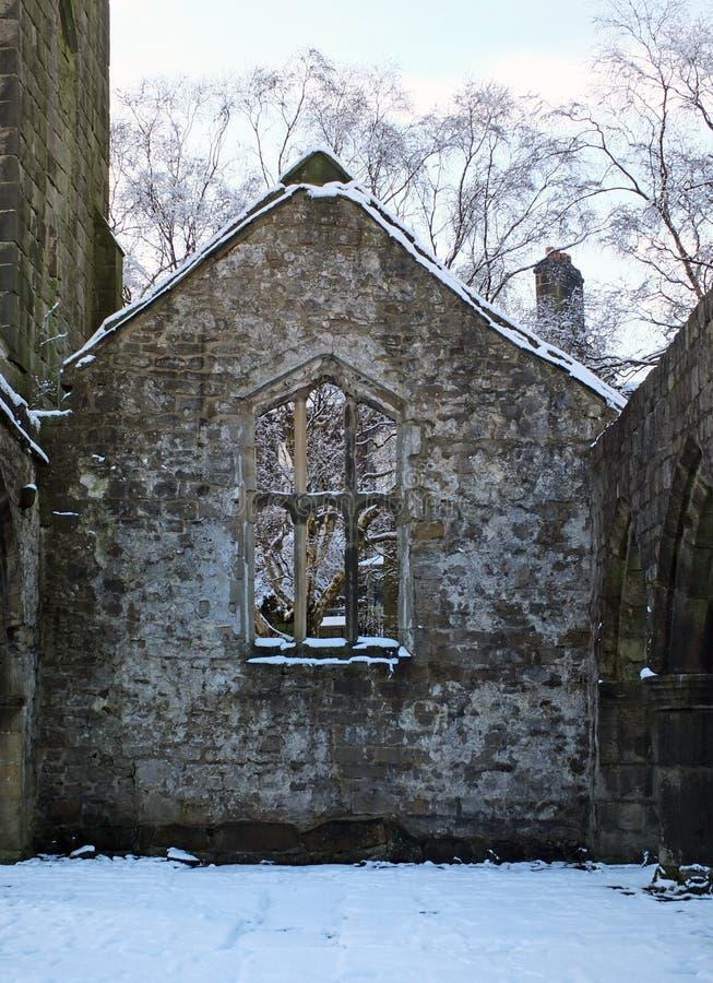 Ansicht durch ein Fenster einer mittelalterlichen ruinierten Kirche im heptonstall Yorkshire mit Schnee bedeckten Bäumen hinter d stockfotos