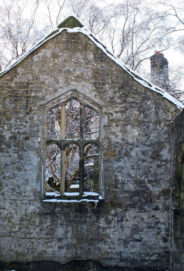 Ansicht durch ein Fenster einer mittelalterlichen ruinierten Kirche im heptonstall Yorkshire mit Schnee bedeckten B?umen hinter d lizenzfreie stockfotografie