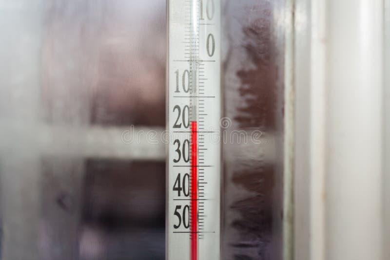 Ansicht durch gefrorenes Fenster vom Haus zum Thermometer im Freien stockfotografie