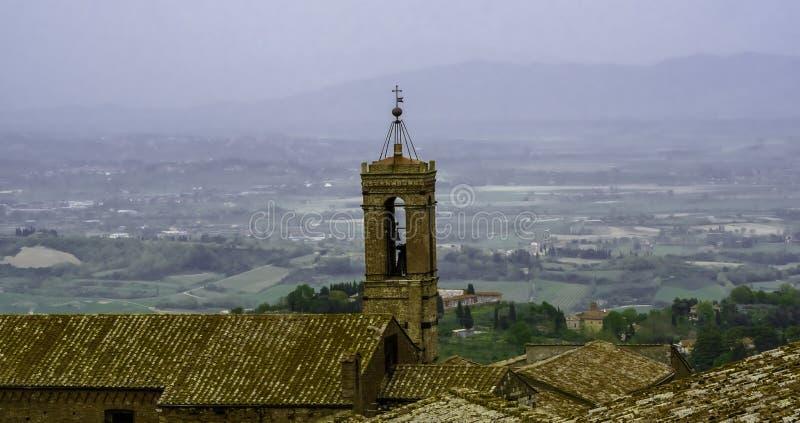 Ansicht eines Glockenturms der Stadt von Montepulciano, mit der Chiantilandschaft im Hintergrund stockbilder
