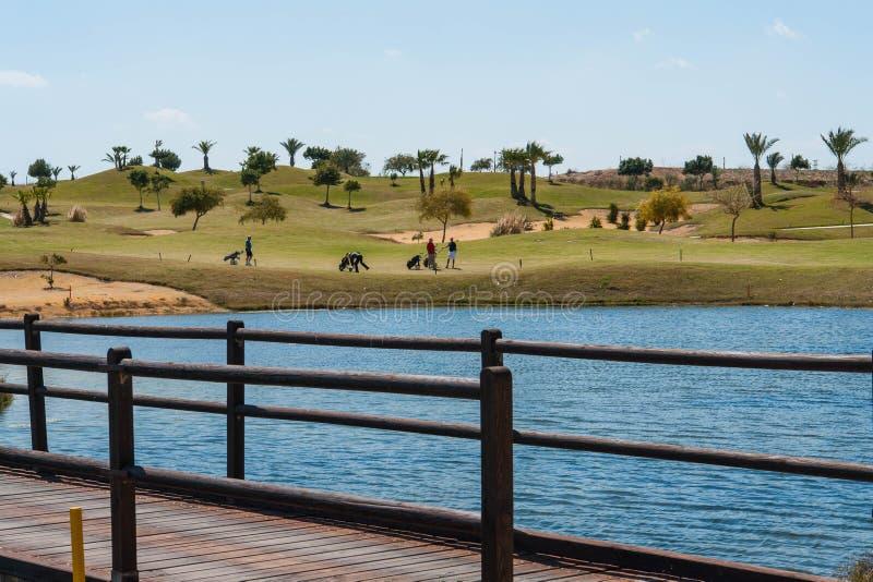 Ansicht eines Golfplatzes auf Costa Blanca mit See, Holzbrücke und Golfspielern an einem Sommertag stockfotos