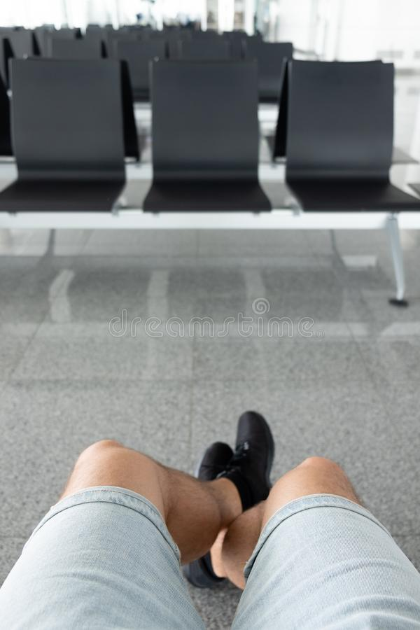 Ansicht eines man& x27; s-Beine, die im Warteraum am Flughafen sitzen lizenzfreie stockfotos