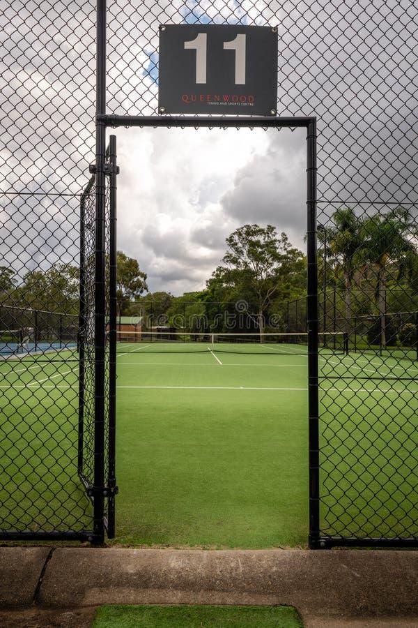 Ansicht eines Tennisplatzes durch das offene Tor in einem Zaun zum Gericht stockbilder