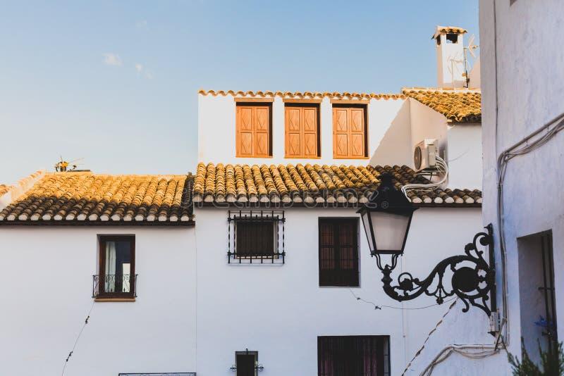 Ansicht eines weißen Hauses mit einem mit Ziegeln gedeckten Dach und Balkonen und der geschmiedeten Laterne in der alten Stadt vo stockbilder