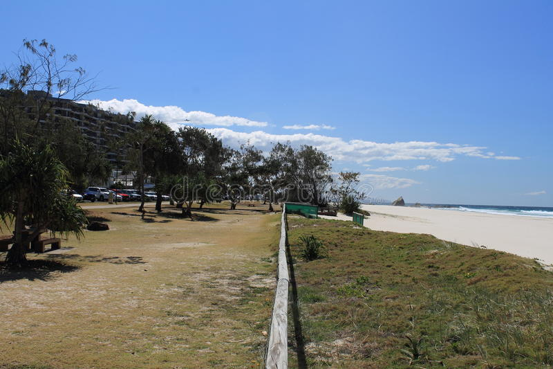 Ansicht entlang eine Zaunschiene zwischen dem Ufer und dem Strand stockfotografie