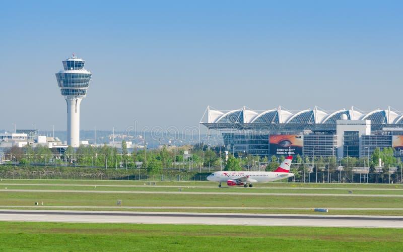 Ansicht internationalen Flughafens Münchens mit Passagierflugzeug von Austrian Airlines lizenzfreie stockbilder
