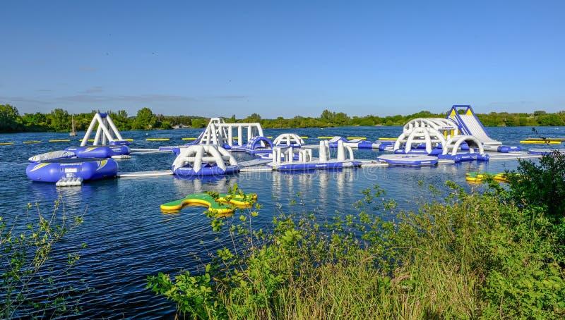 Ansicht sich hin- und herbewegenden Hindernislaufs Aqua Bounces, eben installiert auf den See an Fairlop-Wasser stockbild