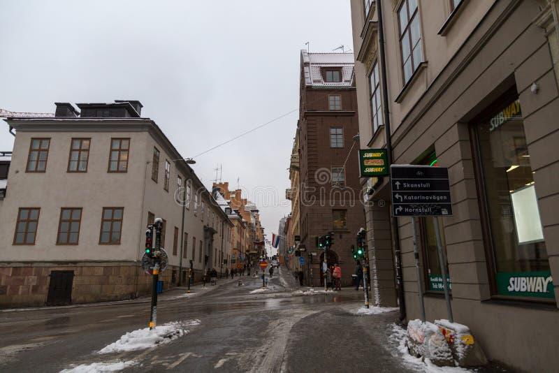 Ansicht Stockholms Schweden, der Straße der Stadt mit dem schmelzenden Schnee und heller Verkehr lizenzfreie stockbilder