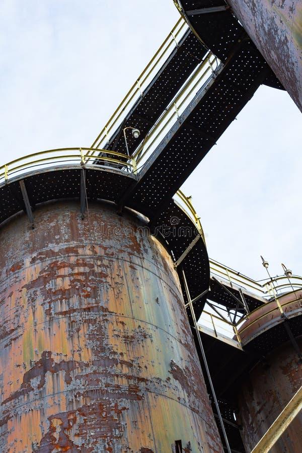 Ansicht unter von den Gehwegen, die zwischen enormen Stapeln eines alten Stahlwerks, schwer verrostete Metallpatina überspannen stockbild