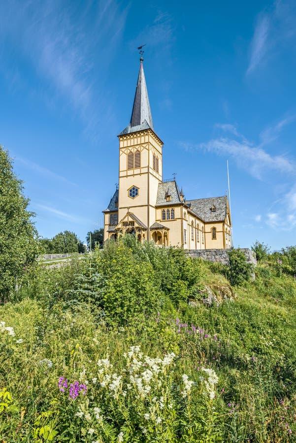 Ansicht an Vagan-Kirche, nannte Lofoten-Kathedrale, von der Steigung, die mit Grünpflanzen und Blumen umfasst wurde Kabelvag-Dorf stockbilder