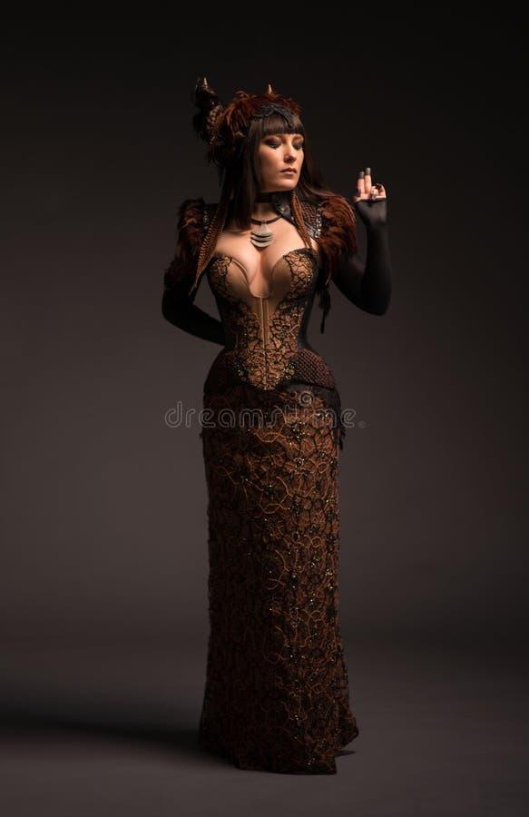Ansicht in voller Länge der Brunettefrau in gotischem steampunk Kleid stockfoto