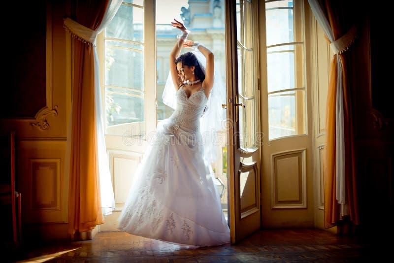 Ansicht in voller Länge der jungen attraktiven reizend Braut im herrlichen Hochzeitskleid, das nahe dem Fenster vom alten aufwirf lizenzfreies stockfoto