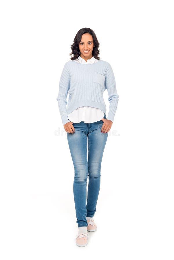 Ansicht in voller Länge der schönen Afroamerikanerfrau, die mit den Händen in den Taschen steht und an der Kamera lächelt lizenzfreie stockbilder