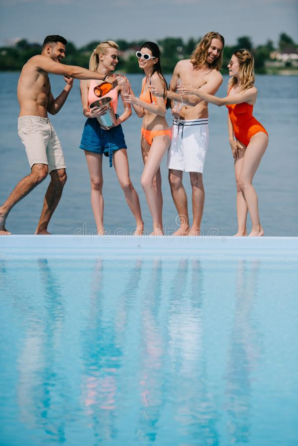 Ansicht in voller Länge des glücklichen jungen Mannes und der Freundinnen, die Champagner am Poolside trinken lizenzfreie stockbilder