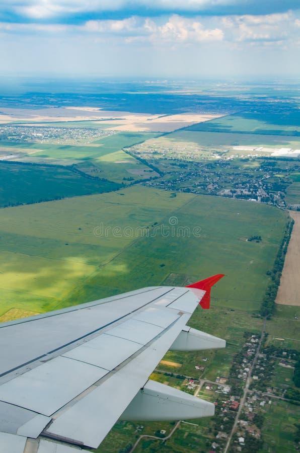 Ansicht vom Fenster der Fläche zu den Städten und zu den Feldern stockfoto