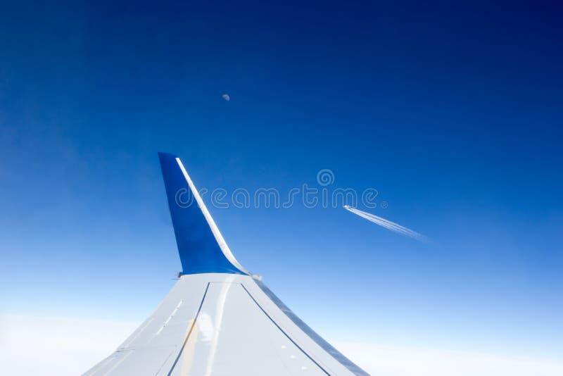 Ansicht vom Flugzeugfenster zum Flügel und andere planieren Fliegen vorbei im Abstand lizenzfreie stockfotos