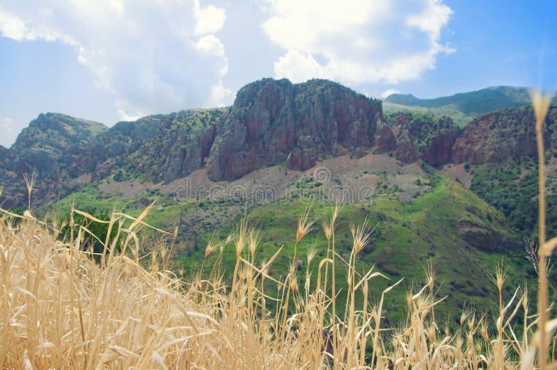 Ansicht vom Kloster von Noravank auf roten Bergen, grünen Hügeln und blauem Himmel stockfotografie