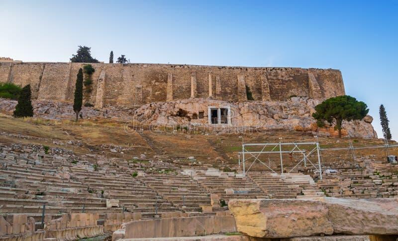 Ansicht von Akropoliswänden und von Hügelsteigungen und Theater von Dionysus in Athen, Griechenland bei Sonnenuntergang lizenzfreies stockfoto
